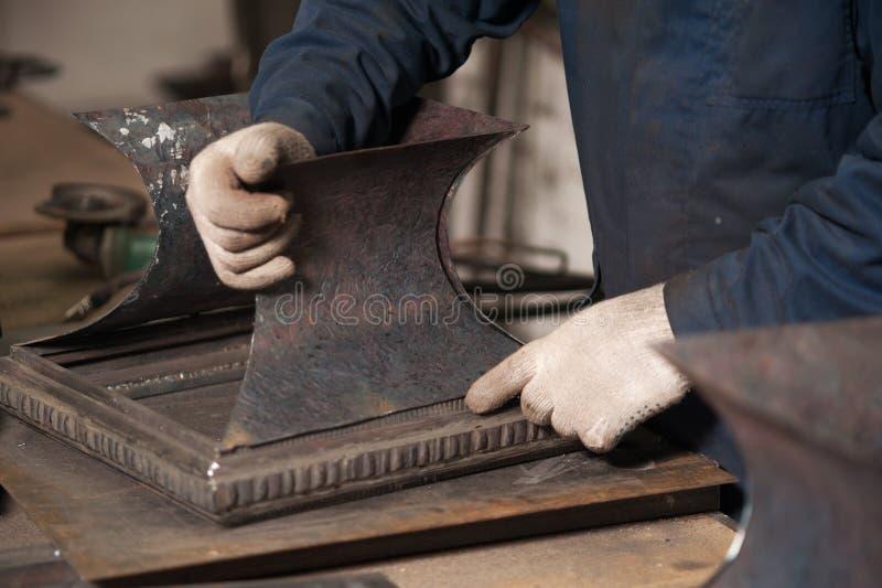 Fermez-vous du forgeron tenant une plaque de métal photographie stock libre de droits