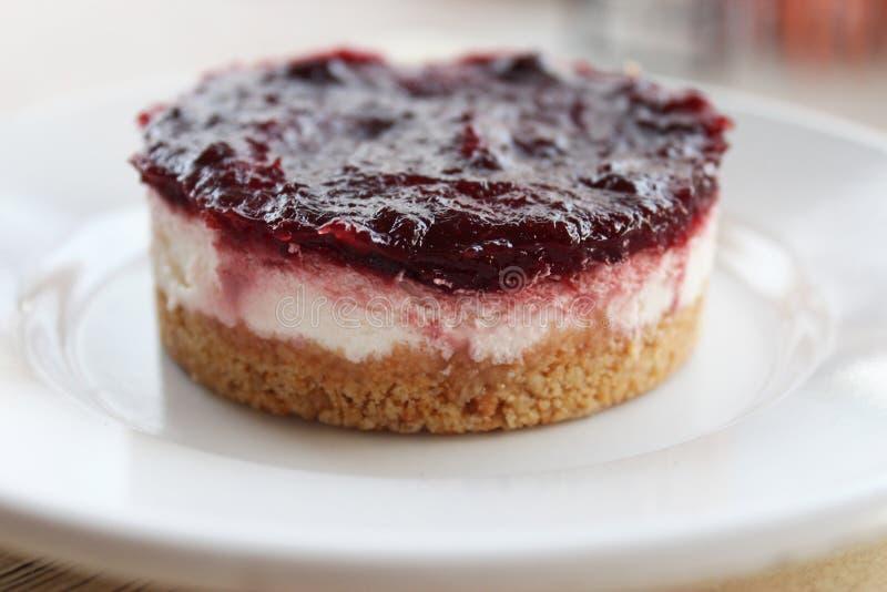 Fermez-vous du gâteau au fromage crémeux avec le bonbon à baie sur le dessus image stock