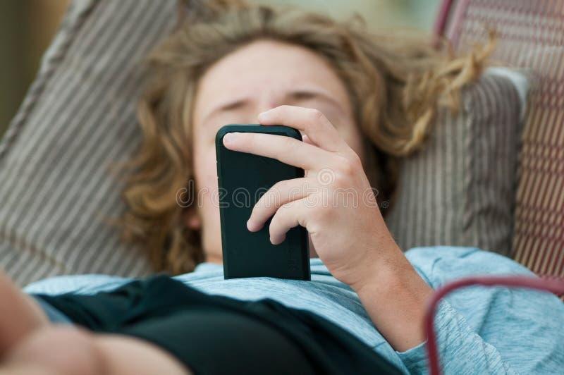Fermez-vous du garçon de l'adolescence au téléphone portable photo libre de droits