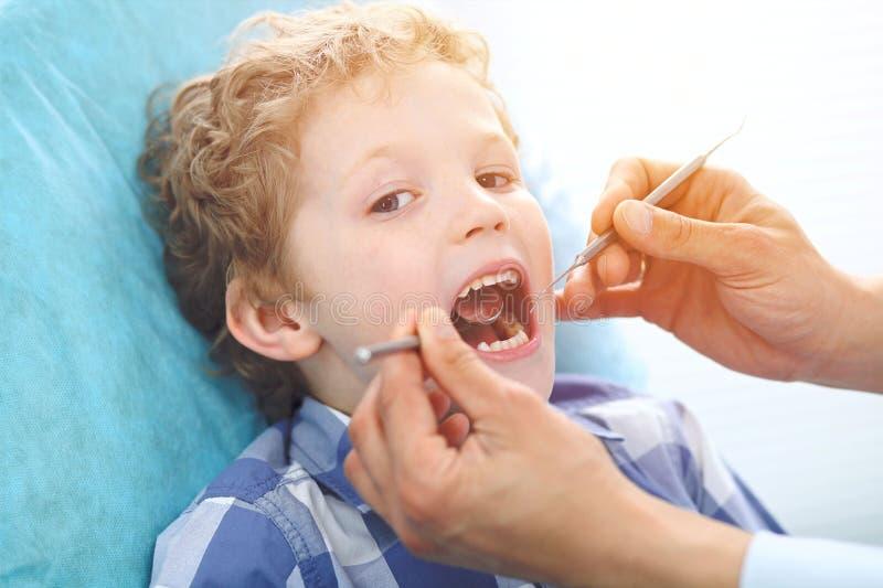 Fermez-vous du garçon faisant examiner ses dents par un dentiste photos libres de droits