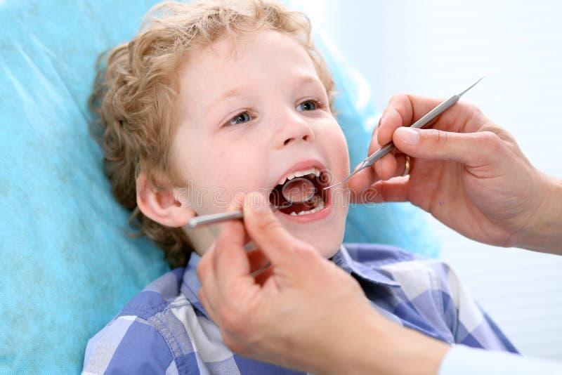 Fermez-vous du garçon faisant examiner ses dents par un dentiste photo stock