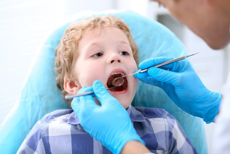 Fermez-vous du garçon faisant examiner ses dents par un dentiste photographie stock