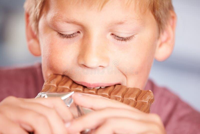 Fermez-vous du garçon mangeant la barre du chocolat photo stock