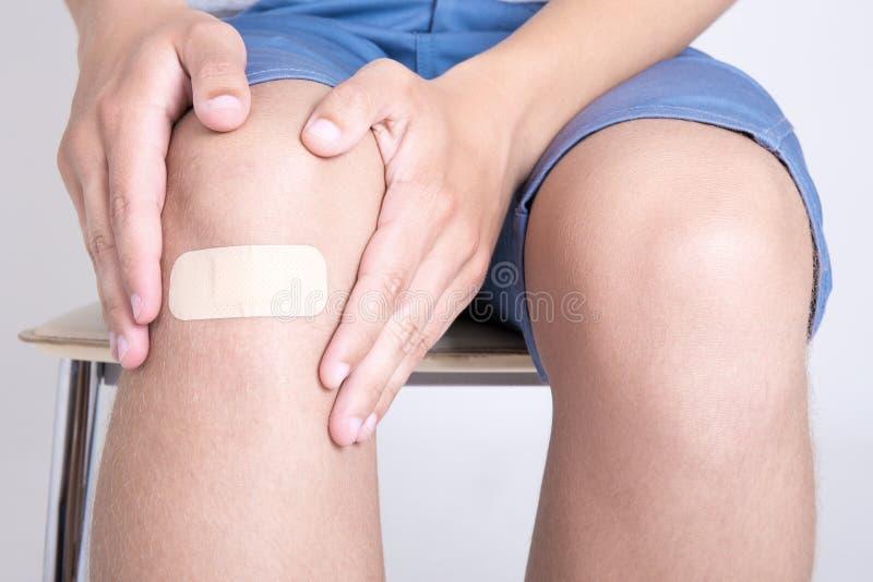 Fermez-vous du genou masculin avec l'emplâtre adhésif photos libres de droits