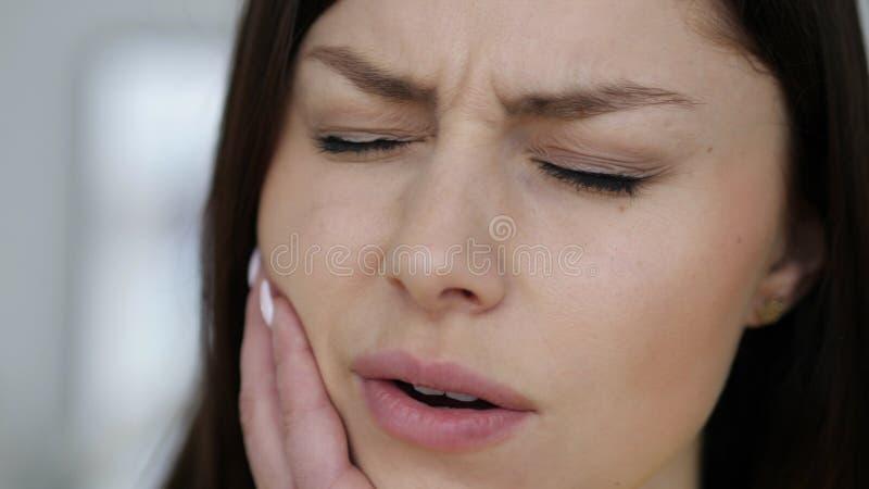 Fermez-vous du geste de mal de dents par la jeune femme, visage photos libres de droits