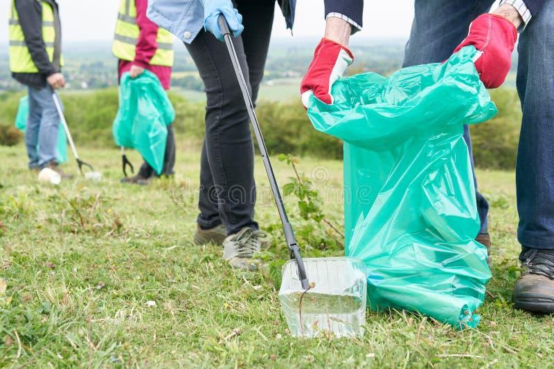 Fermez-vous du groupe d'aînés utiles rassemblant des ordures dans la campagne images stock