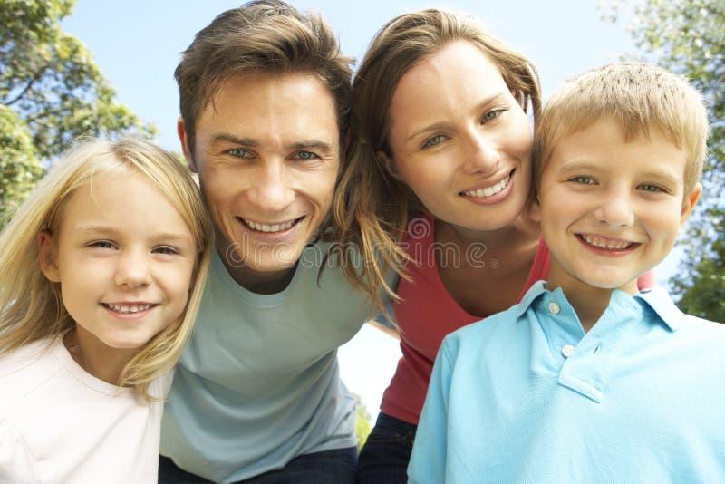 Fermez-vous du groupe de famille regardant dans l'appareil-photo en parc photographie stock
