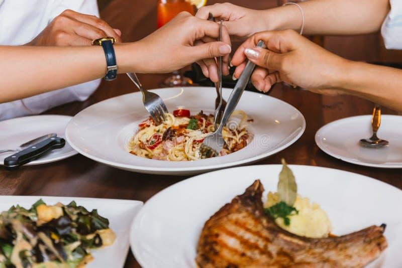 Fermez-vous du groupe de mains d'amis avec une fourchette ayant l'amusement mangeant et dînant italien ensemble photos stock