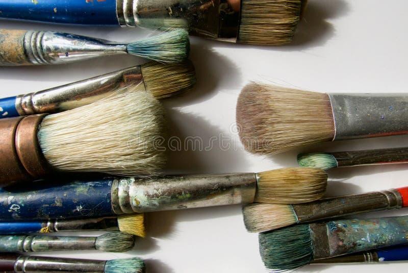 Fermez-vous du groupe de pinceaux du ` s d'artiste montrant leurs poils souillés photos libres de droits