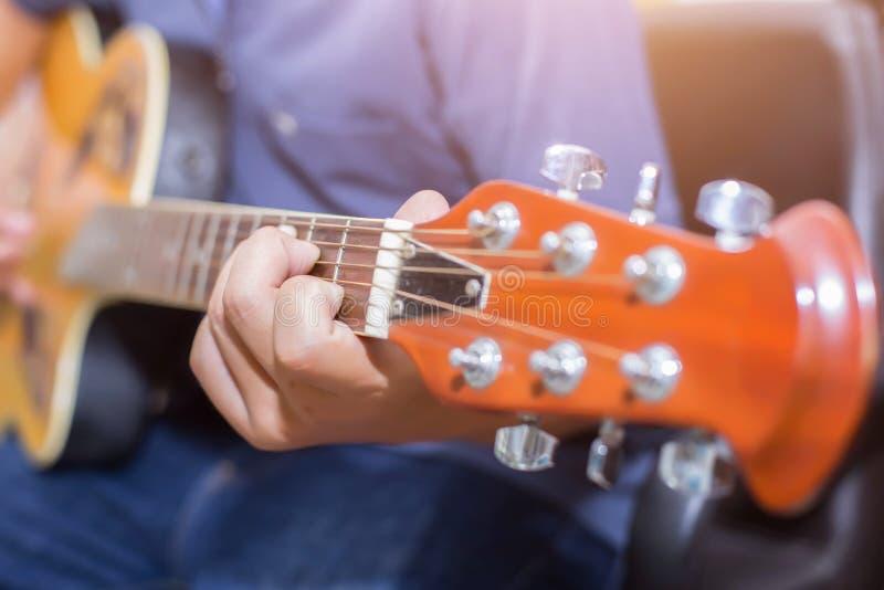 Fermez-vous du jeune hippie que la femme a pratiqué la guitare en parc, heureux et ayez plaisir à jouer la guitare photos stock