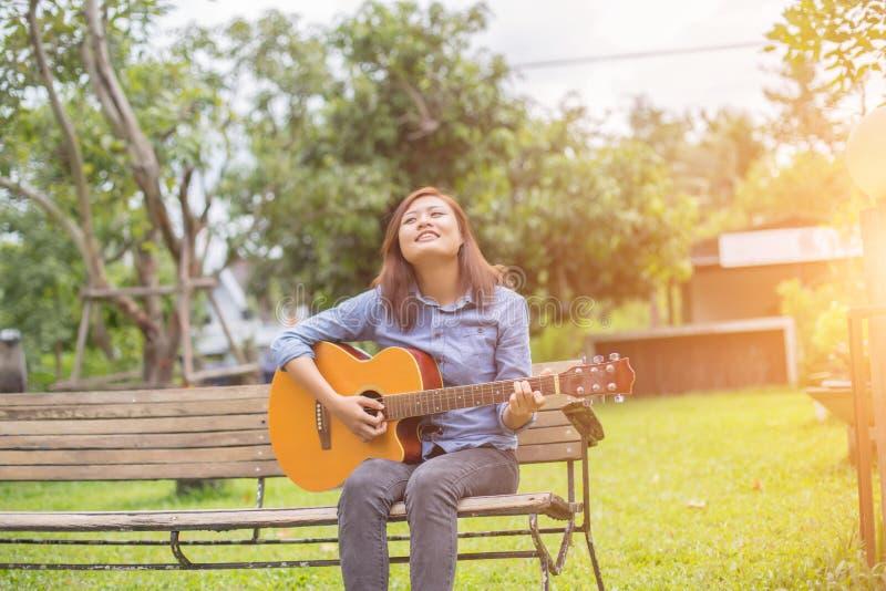 Fermez-vous du jeune hippie que la femme a pratiqué la guitare en parc, heureux et ayez plaisir à jouer la guitare images libres de droits