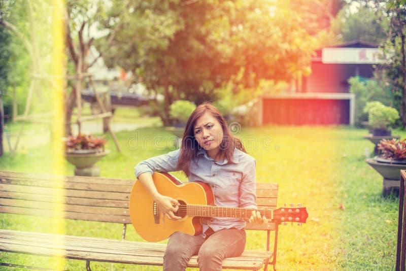 Fermez-vous du jeune hippie que la femme a pratiqué la guitare en parc, heureux et ayez plaisir à jouer la guitare photographie stock libre de droits