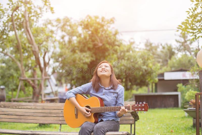 Fermez-vous du jeune hippie que la femme a pratiqué la guitare en parc, heureux et ayez plaisir à jouer la guitare image stock