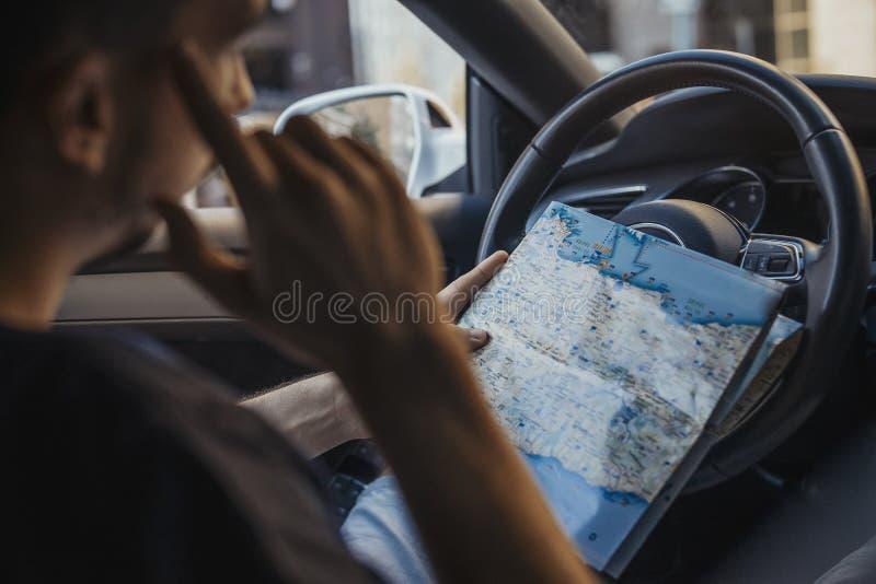 Fermez-vous du jeune homme regardant la carte derrière la roue dans la voiture images stock
