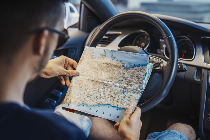 Fermez-vous du jeune homme regardant la carte derrière la roue dans la voiture photos libres de droits