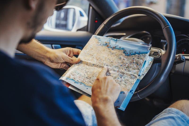 Fermez-vous du jeune homme regardant la carte derrière la roue dans la voiture photographie stock