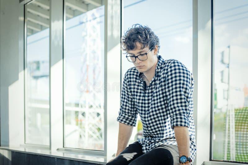 Fermez-vous du jeune homme s'asseyant à côté de grandes fenêtres à la station de métro photo stock