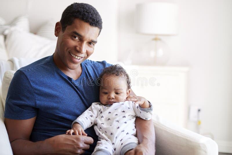 Fermez-vous du jeune père adulte d'Afro-américain s'asseyant dans un fauteuil tenant son vieux fils de trois mois de bébé, en sou photos libres de droits