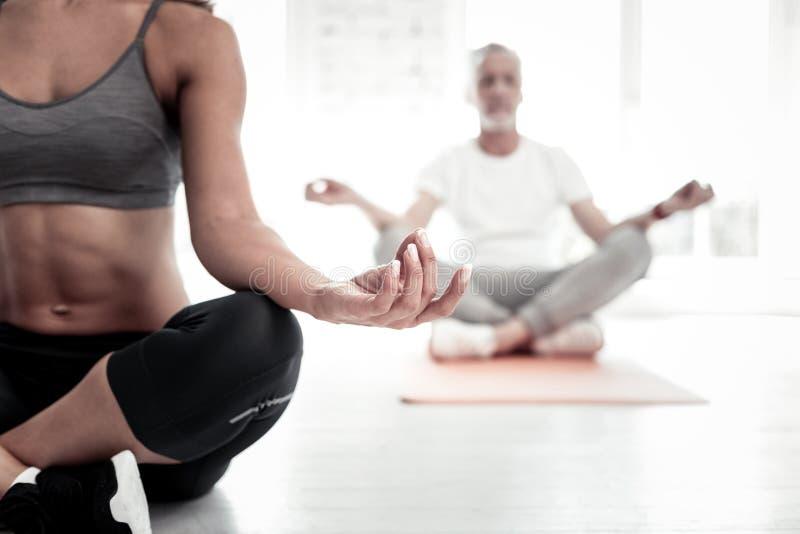 Fermez-vous du jeune professeur féminin de yoga méditant photographie stock