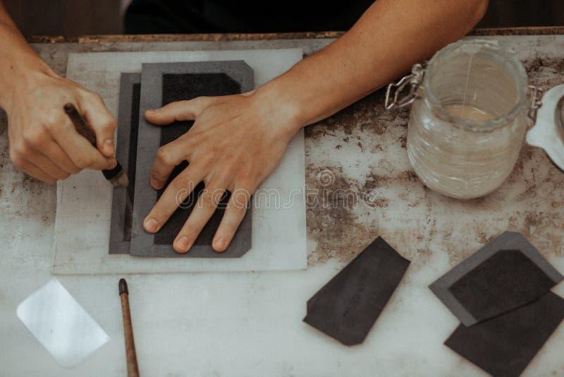 Fermez-vous du maître faisant le portefeuille en cuir avec la brosse et la colle Maître fait main au travail dans l'atelier local images stock
