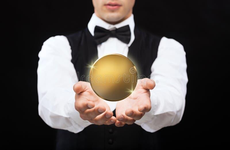 Fermez-vous du magicien avec la pièce de monnaie d'or au-dessus du noir image stock