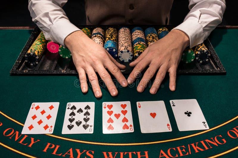 Fermez-vous du marchand de holdem avec jouer des cartes et des puces sur la table verte photographie stock