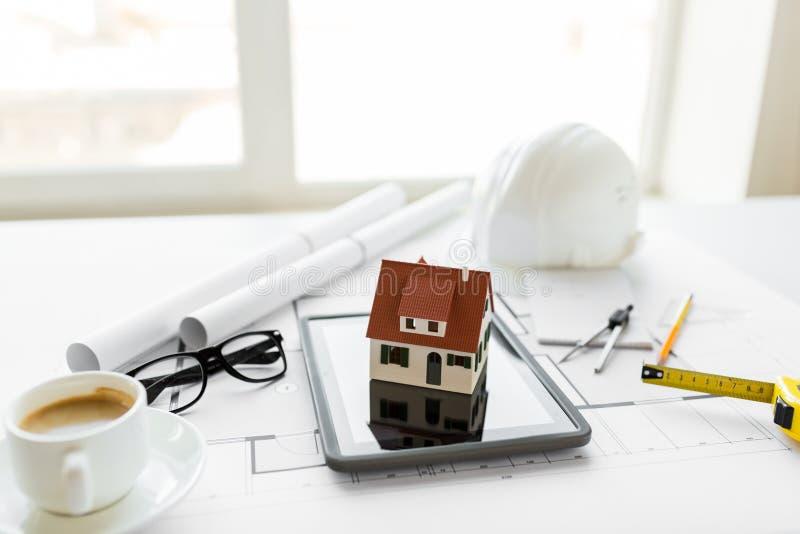 Fermez-vous du modèle vivant de maison sur le PC de comprimé photos stock