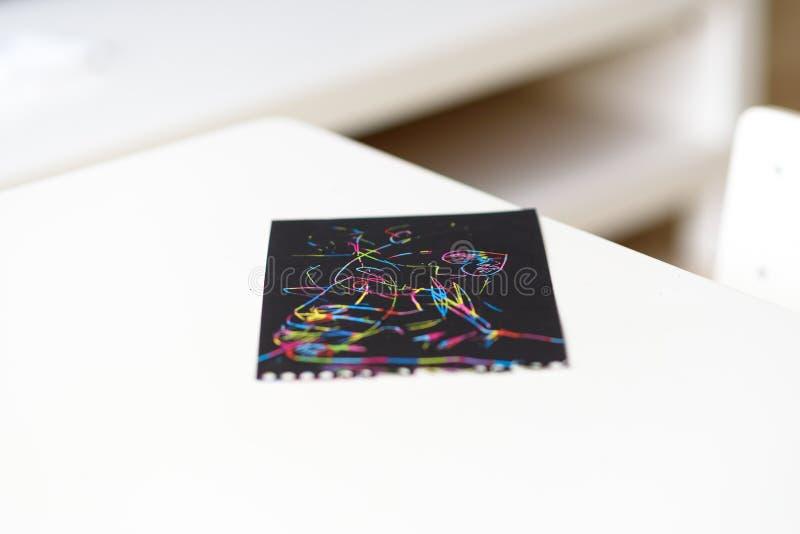 Fermez-vous du papier de peinture d'éraflure magique sur la table blanche à la maison photo libre de droits