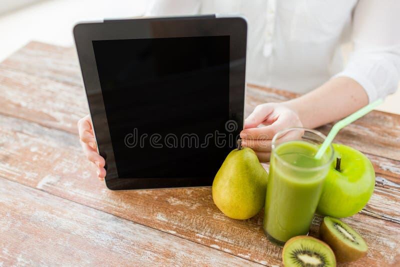Fermez-vous du PC de comprimé de mains de femme et du jus de fruit photographie stock libre de droits
