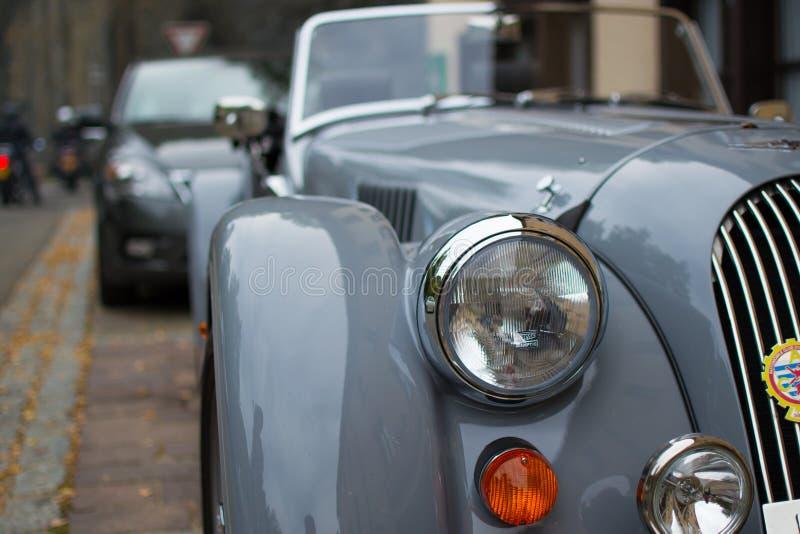Fermez-vous du phare d'une voiture de sport classique grise, avec le fond brouillé image stock