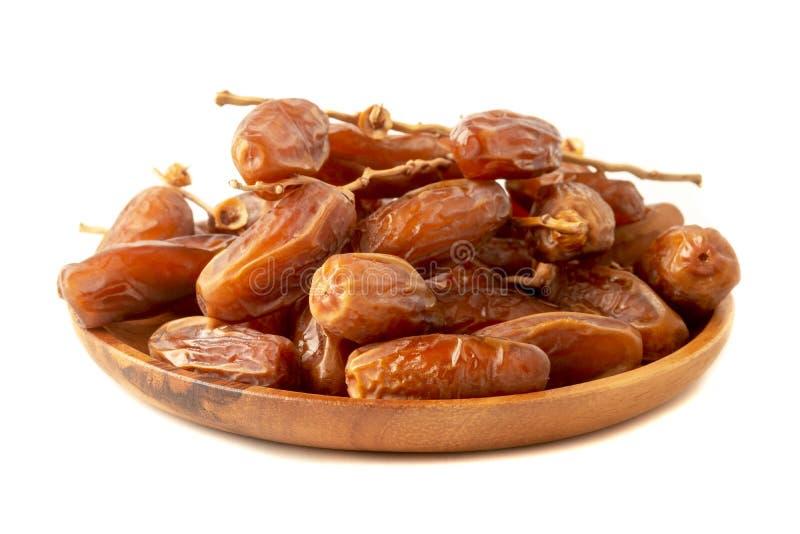 Fermez-vous du plam de dates de groupe Plam frais de dates dans le plateau en bois au-dessus du fond blanc image stock