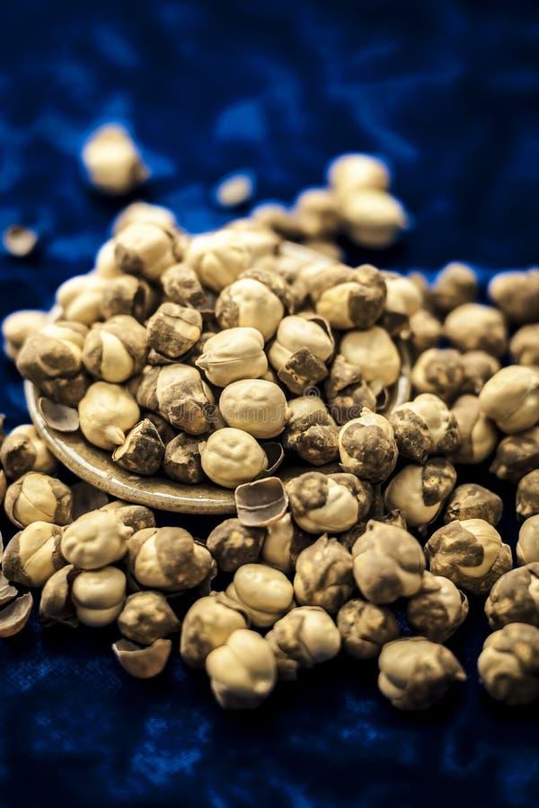 Fermez-vous du pois chiche/du channa ou de la Dalia cuit au four ou r?ti dans une cuvette sur une surface bleue photos stock