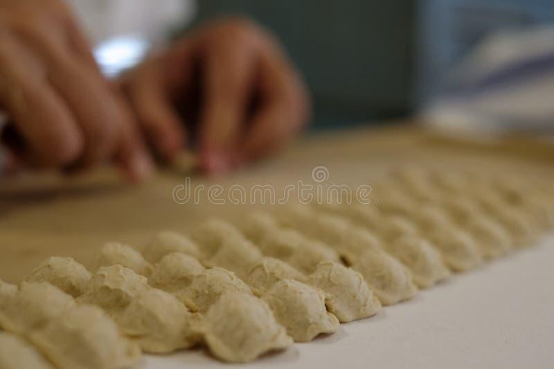 Fermez-vous du procédé de pastification La femme fait l'orecchiette, pâtes auriformes, traditionnelles à la région de la Puglia d photos stock