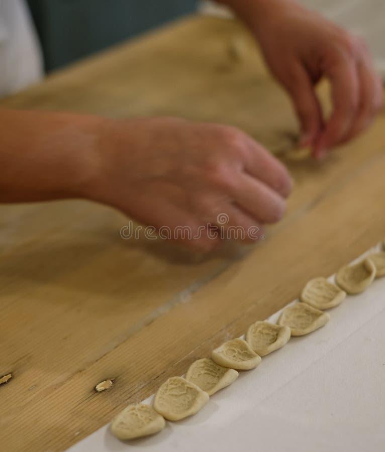 Fermez-vous du procédé de pastification La femme fait l'orecchiette, pâtes auriformes, traditionnelles à la région de la Puglia d photos libres de droits