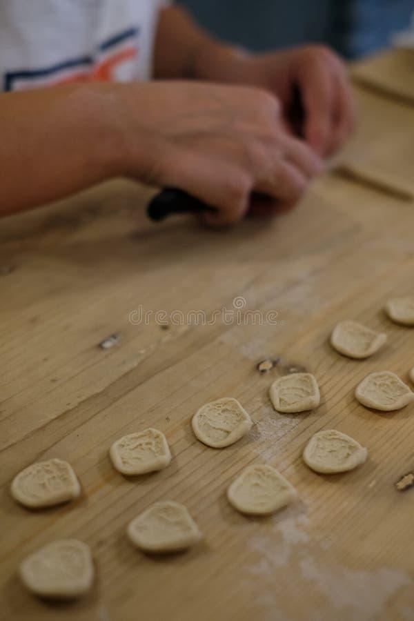 Fermez-vous du procédé de pastification La femme fait l'orecchiette, pâtes auriformes, traditionnelles à la région de la Puglia d photographie stock