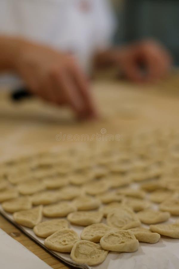 Fermez-vous du procédé de pastification La femme fait l'orecchiette, pâtes auriformes, traditionnelles à la région de la Puglia d images stock