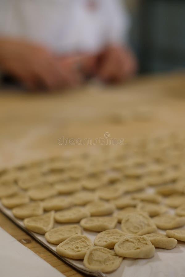 Fermez-vous du procédé de pastification La femme fait l'orecchiette, pâtes auriformes, traditionnelles à la région de la Puglia d image libre de droits