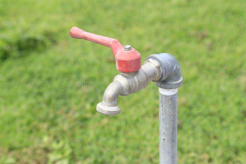 Fermez-vous du robinet d'eau avec le fond d'herbe verte - sélectif photo stock