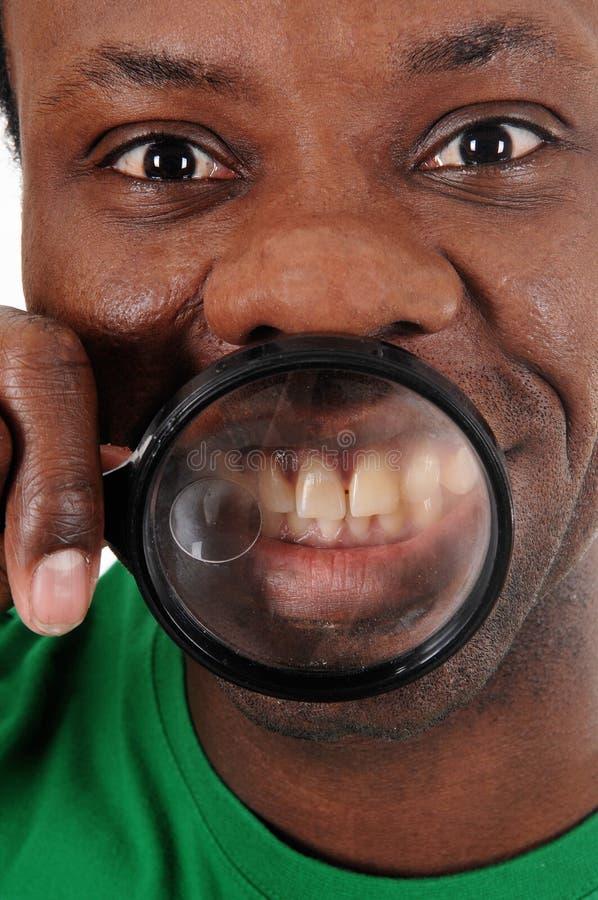 Fermez-vous du ` s de visage et de dents de l'homme africain photo stock