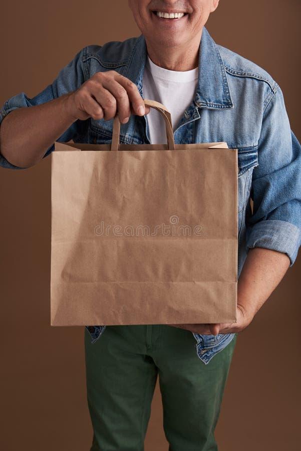 Fermez-vous du sac de papier dans des mains de personne de sourire photo libre de droits