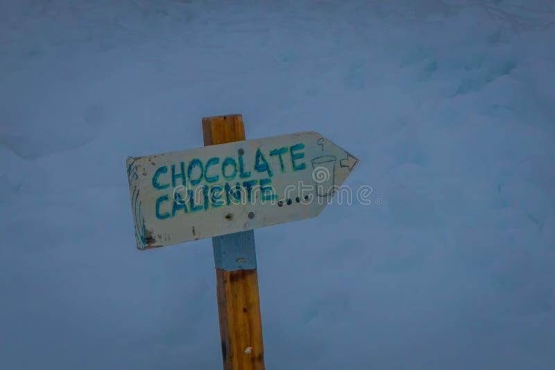 Fermez-vous du signe instructif du chocolat chaud écrit au-dessus d'une structure en bois et de l'indication une direction dans photo libre de droits