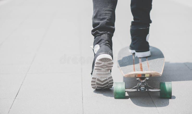 Fermez-vous du skater& x27 ; jambes de s sur l'équitation de longboard à la rue dedans dehors photos stock