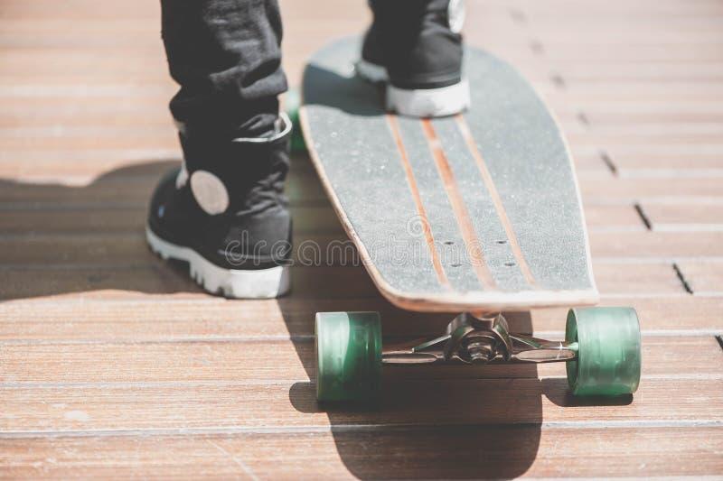 Fermez-vous du skater& x27 ; jambes de s sur l'équitation de longboard à la rue dedans dehors image libre de droits