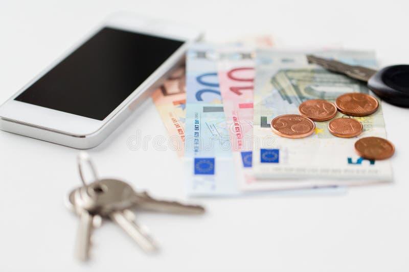 Fermez-vous du smartphone, de l'argent et des clés sur la table photo stock