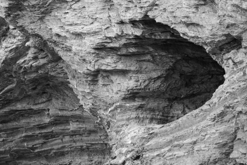 Fermez-vous du trou érodé à l'arrière-plan de texture de roche de falaise en noir et blanc images libres de droits