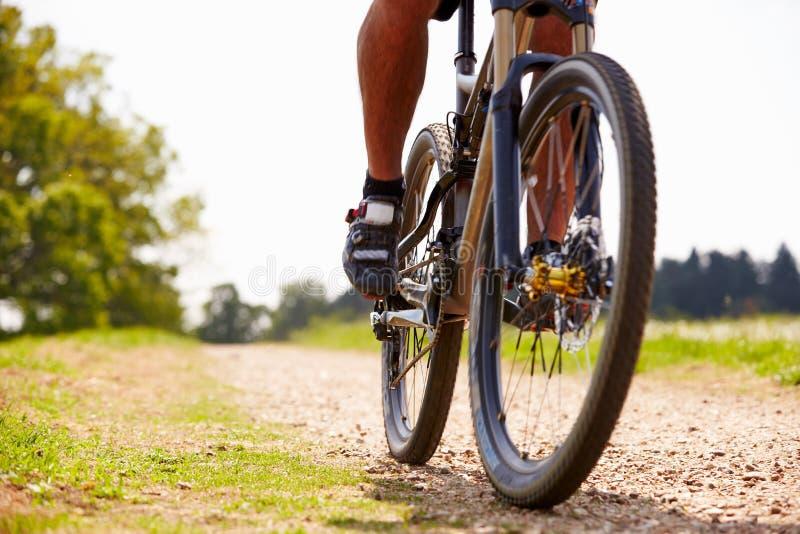 Fermez-vous du vélo de montagne d'équitation de l'homme sur le chemin de campagne photo libre de droits