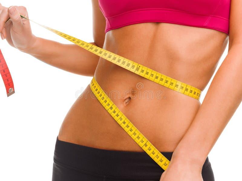 Fermez-vous du ventre qualifié avec la bande de mesure photos stock