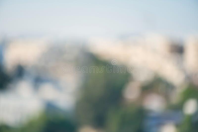 Fermez-vous du verre de vin rouge dans la perspective de la ville brouillée avec le bokeh photographie stock