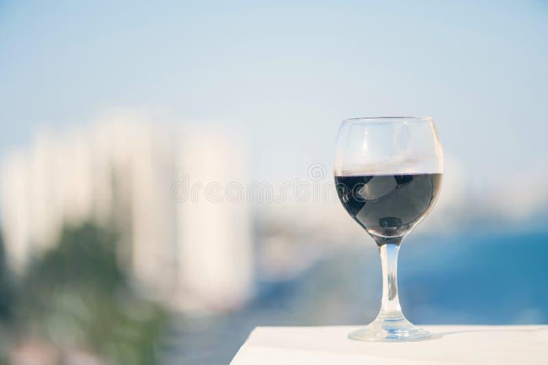 Fermez-vous du verre de vin rouge dans la perspective de la ville brouillée avec le bokeh images libres de droits