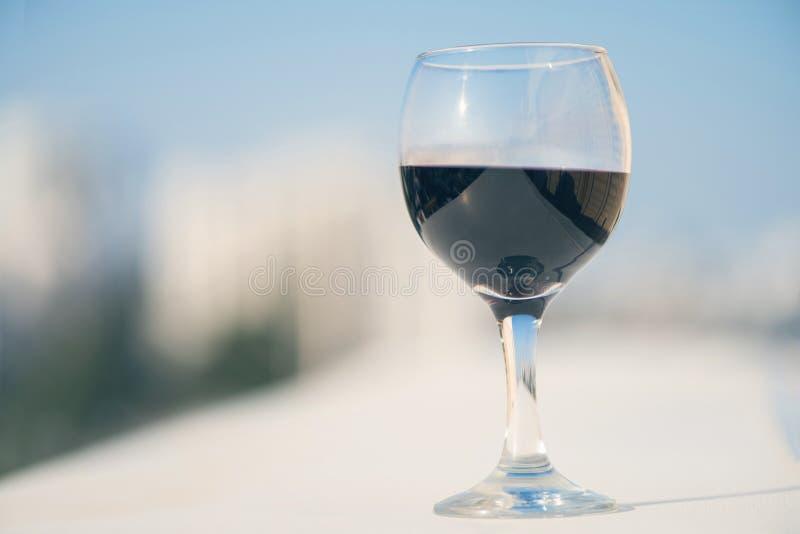 Fermez-vous du verre de vin rouge dans la perspective de la ville brouillée avec le bokeh photos libres de droits